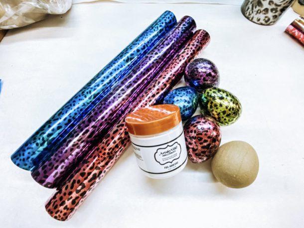 Metallic foils in blue leopard print, purple leopard print and pink leopard print. Paper-mache eggs.
