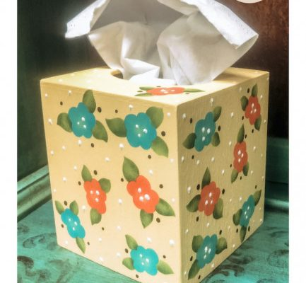A wooden tissue box cover painted with flowers.