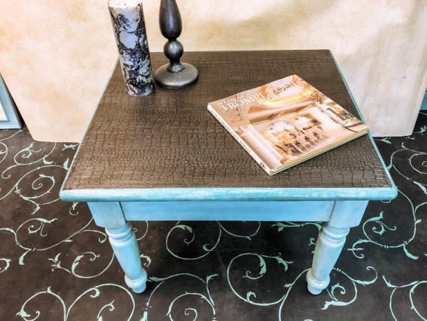 Side table with candle and magazine on it.